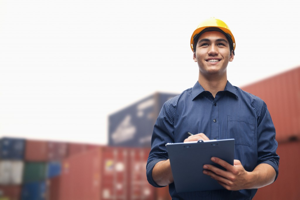 Smiling young engineer in a shipping yard examining cargo